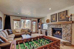 Downstairs Living Area with Big Screen TV and Blazing Gas Fireplace
