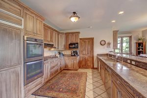 Kitchen has Double Oven, Granite Countertops, and a Gas Range